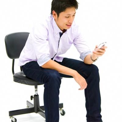 「携帯を操作する青年」の写真素材