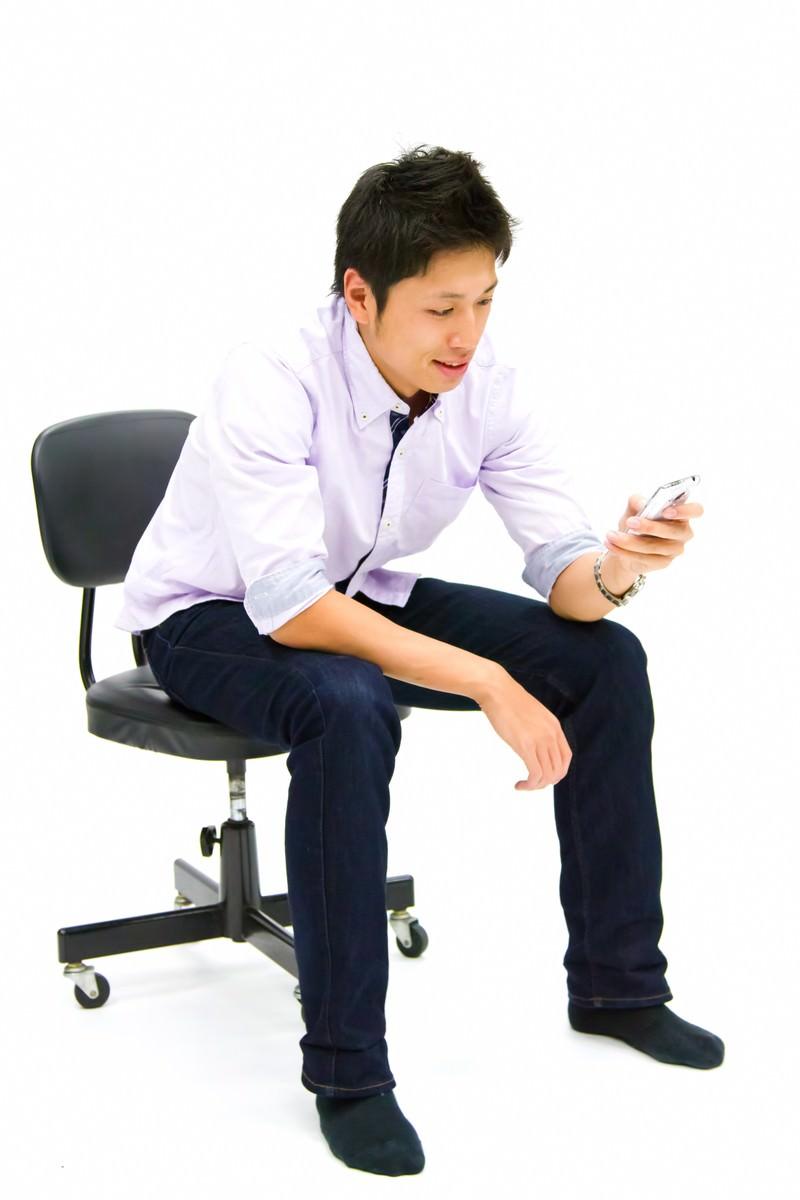 「携帯を操作する青年」の写真[モデル:恭平]