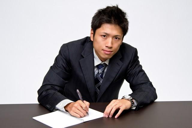 デスクでメモを取るビジネスマンの写真