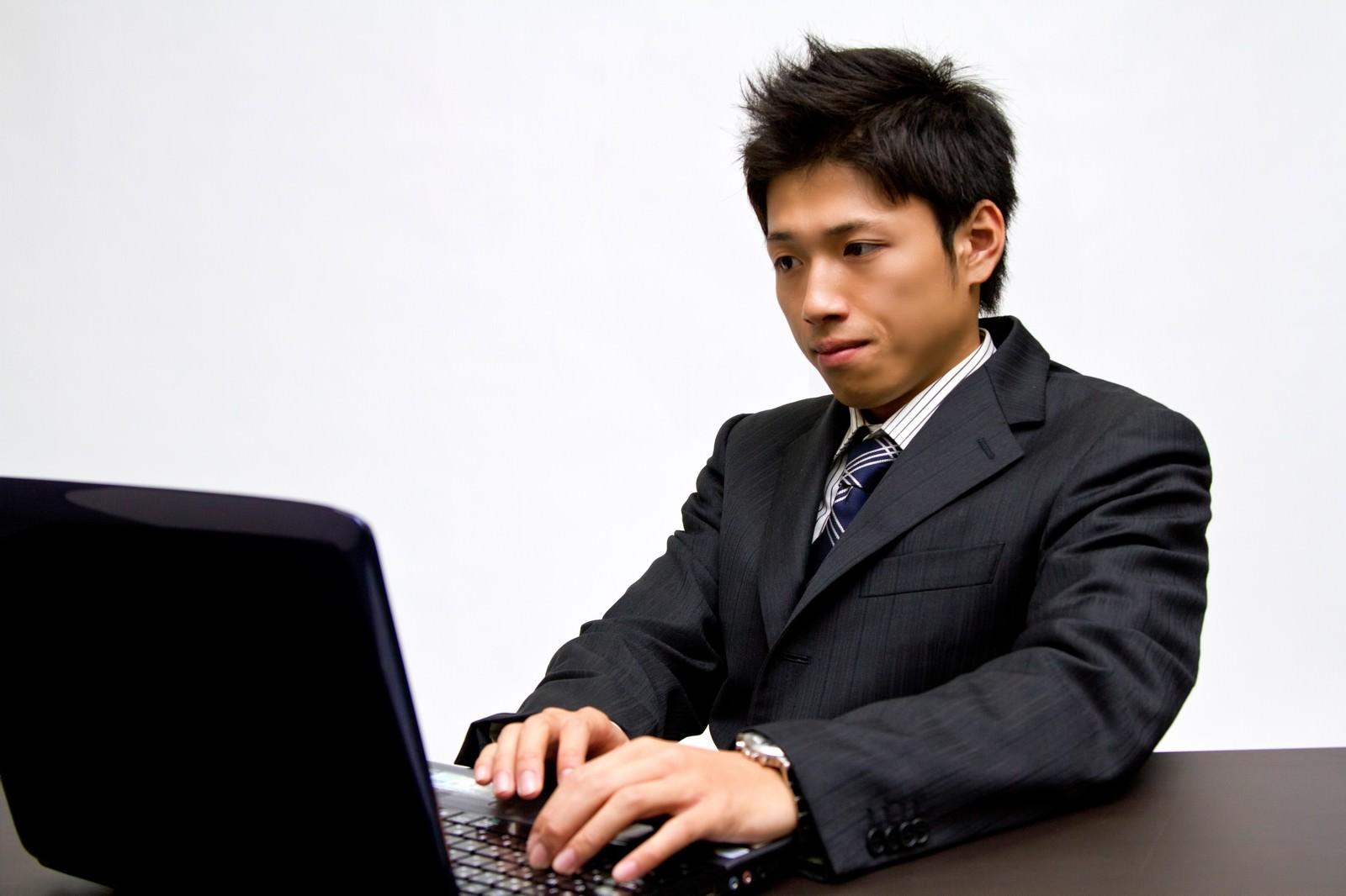 「ノートパソコンで作業中のビジネスマン」の写真[モデル:恭平]