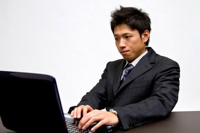 ノートパソコンで作業中のビジネスマンの写真