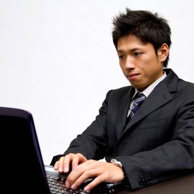 「ノートパソコンで作業中のビジネスマン」の写真素材