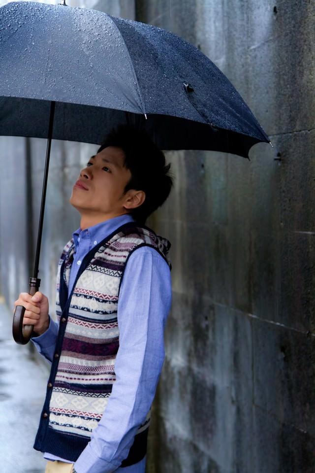 雨の日に傘を差す青年の写真