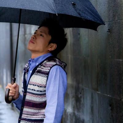 「雨の日に傘を差す青年」の写真素材