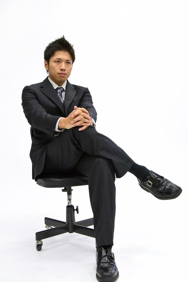 椅子に座って足を組むサラリーマンの写真