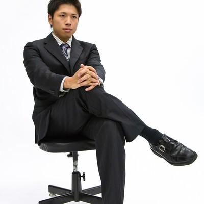 「椅子に座って足を組むサラリーマン」の写真素材