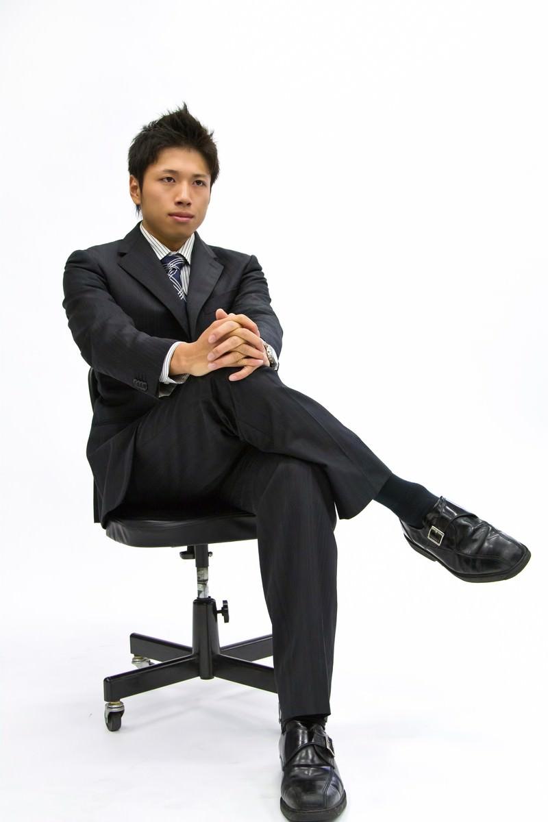「椅子に座って足を組むサラリーマン」の写真[モデル:恭平]