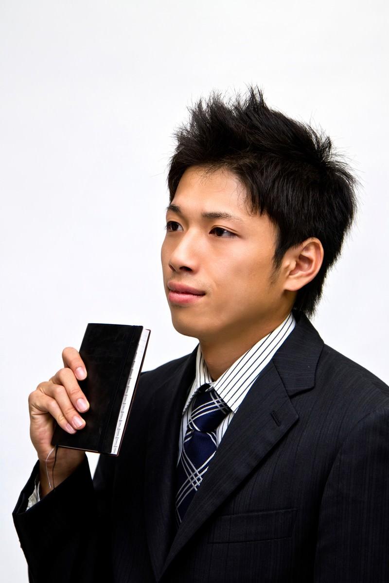 「手帳を見せるサラリーマン」の写真[モデル:恭平]