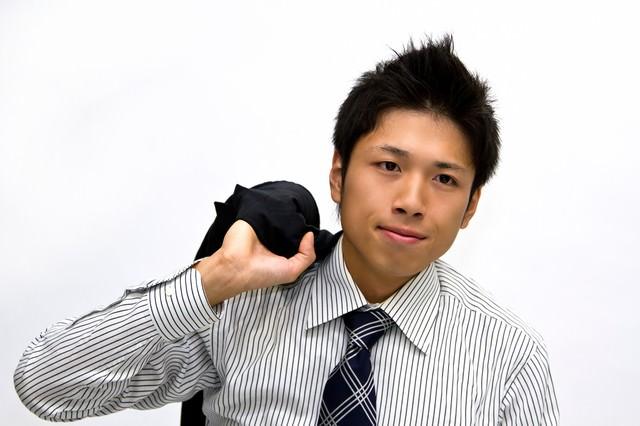 上着を持つネクタイ姿のビジネスマンの写真