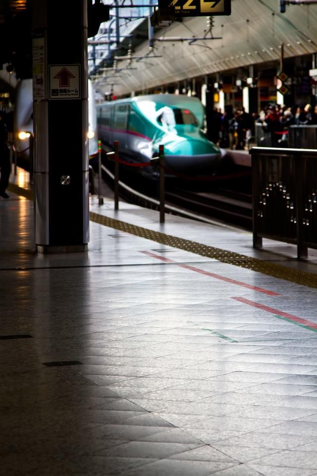 新幹線と混みあうホームの写真