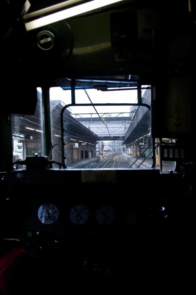 電車の運転席と窓越しのホームの写真