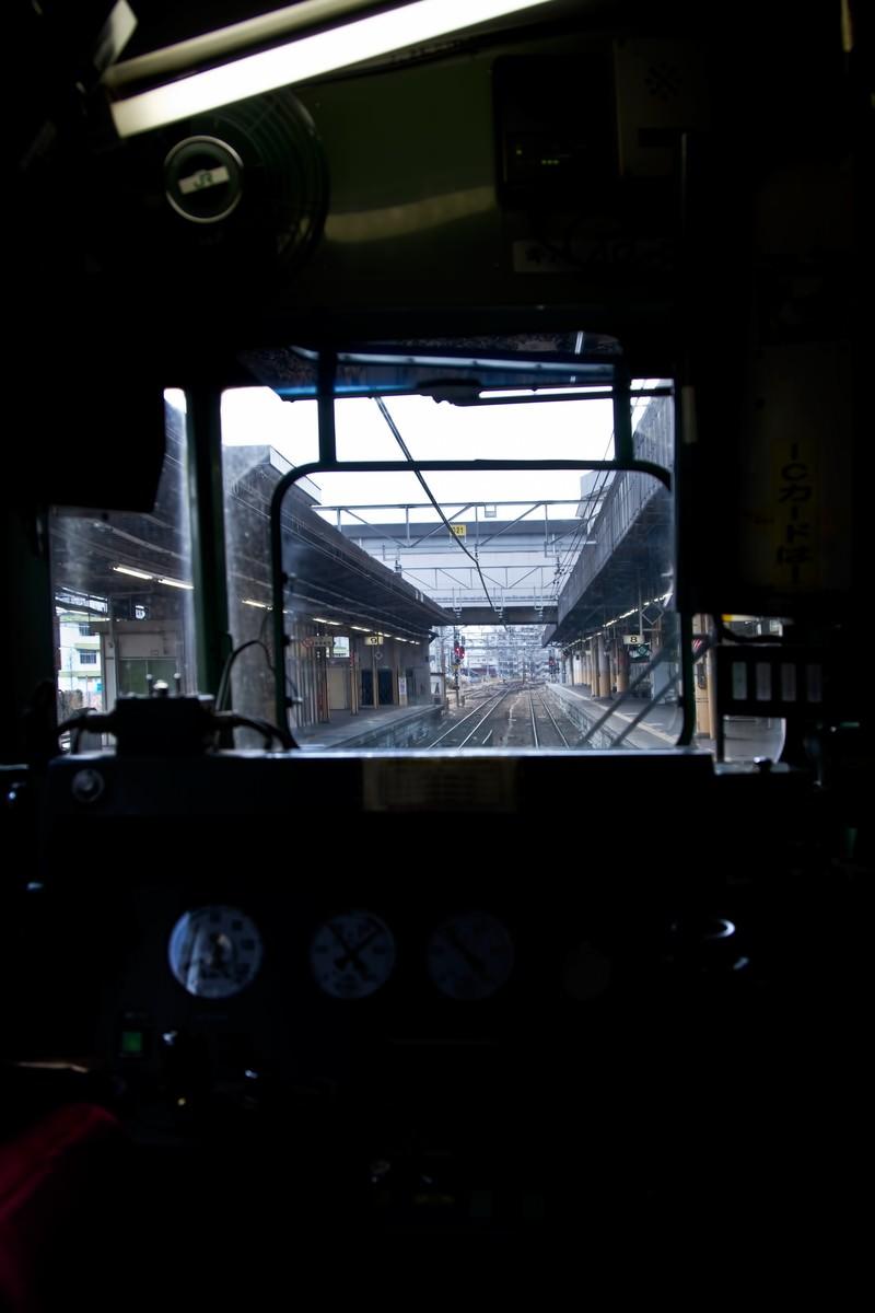 「電車の運転席と窓越しのホーム」の写真