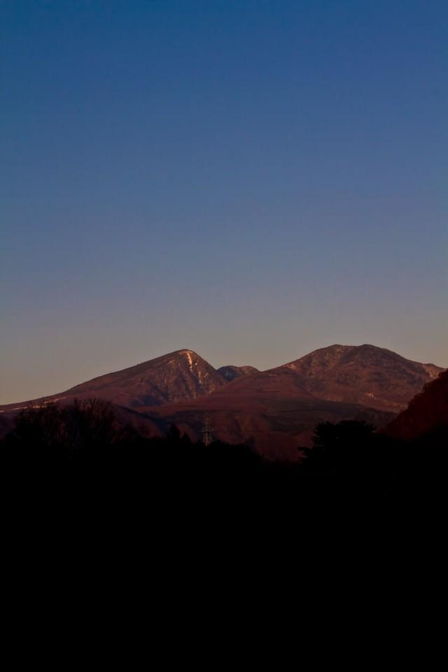 夕暮れ時の雪が残る山の写真