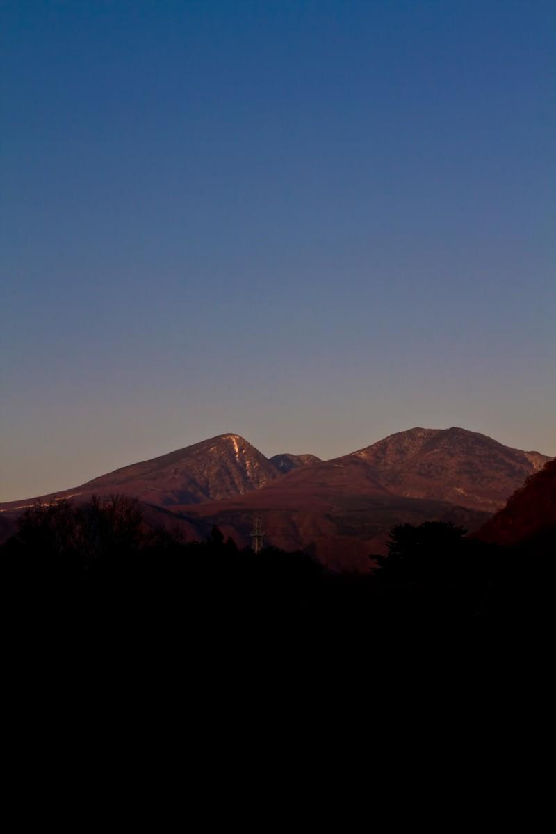 「夕暮れ時の雪が残る山」の写真