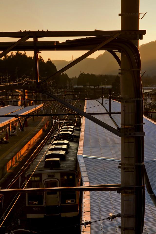 夕暮れのホームと電車の写真