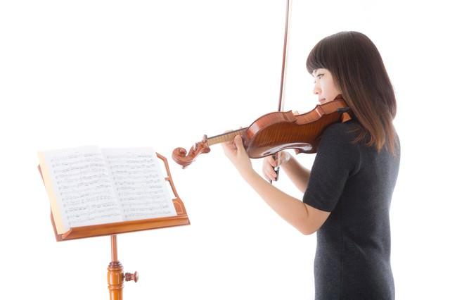 新しい曲を譜読みをする女性の写真