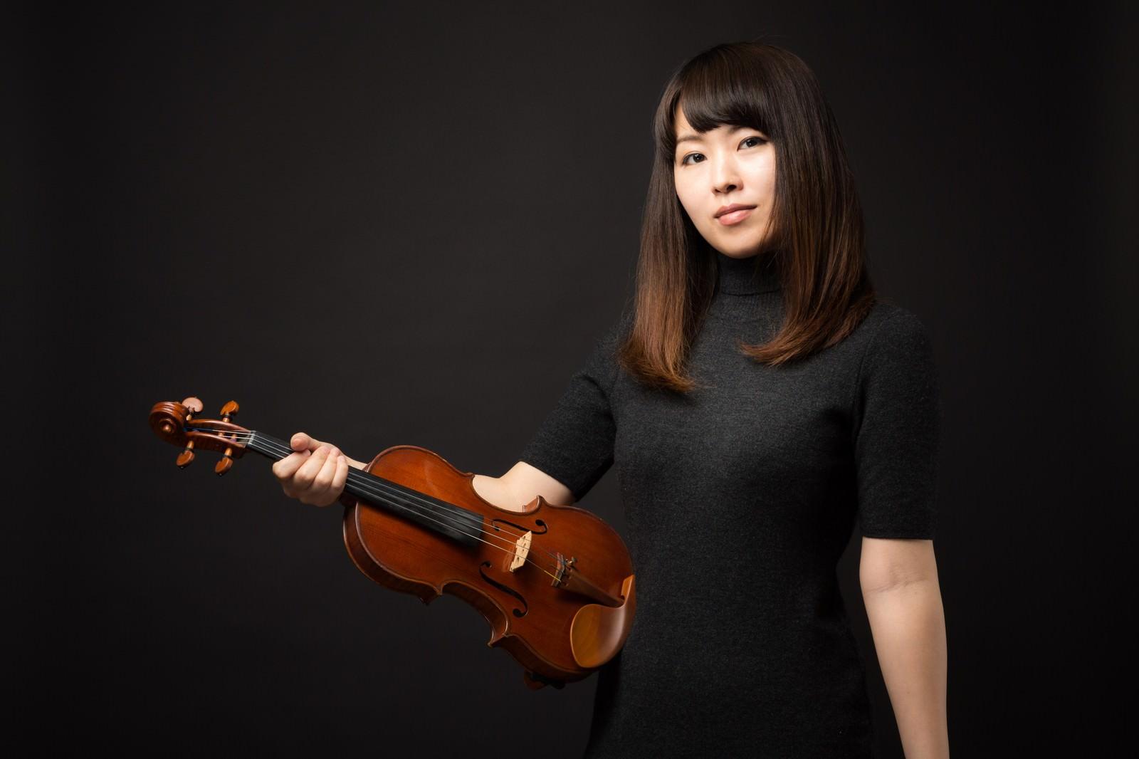 「ヴァイオリンを片手にこちらをみる女性」の写真[モデル:yukiko]