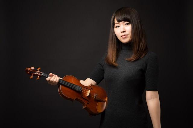 ヴァイオリンを片手にこちらをみる女性の写真