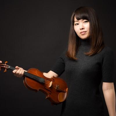 「ヴァイオリンを片手にこちらをみる女性」の写真素材