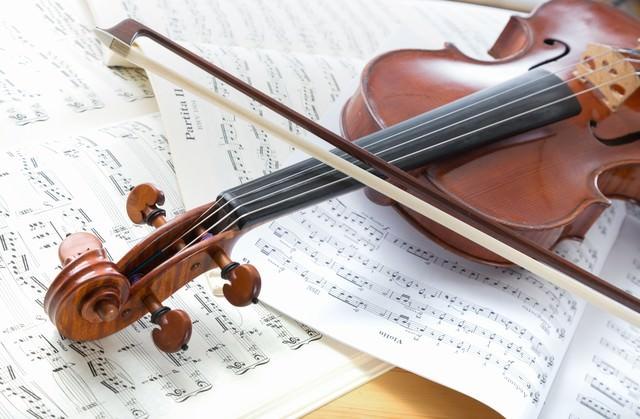 楽譜の上に置かれたヴァイオリンの写真
