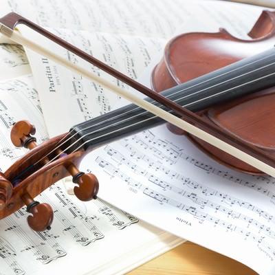 「楽譜の上に置かれたヴァイオリン」の写真素材