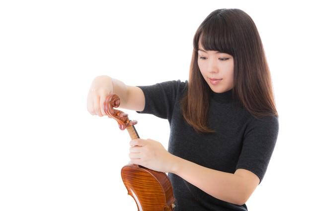 ヴァイオリンの弦を張り替える女性の写真