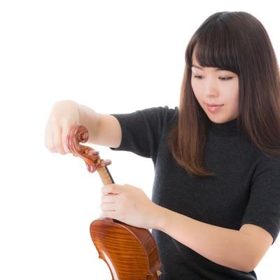 「ヴァイオリンの弦を張り替える女性」の写真素材