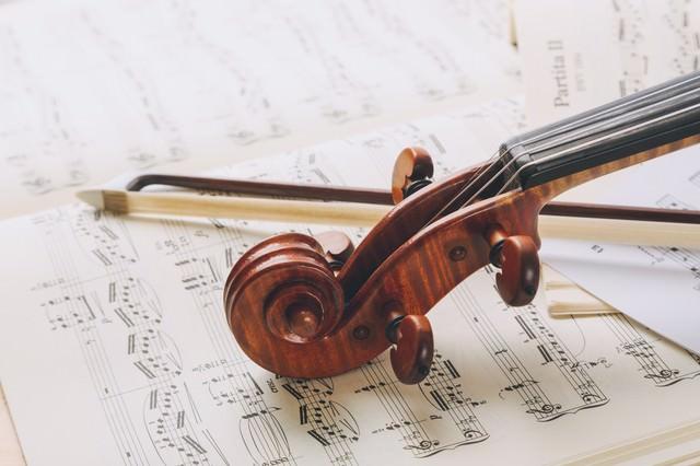 楽譜の上のヴァイオリンのネックと弓の写真