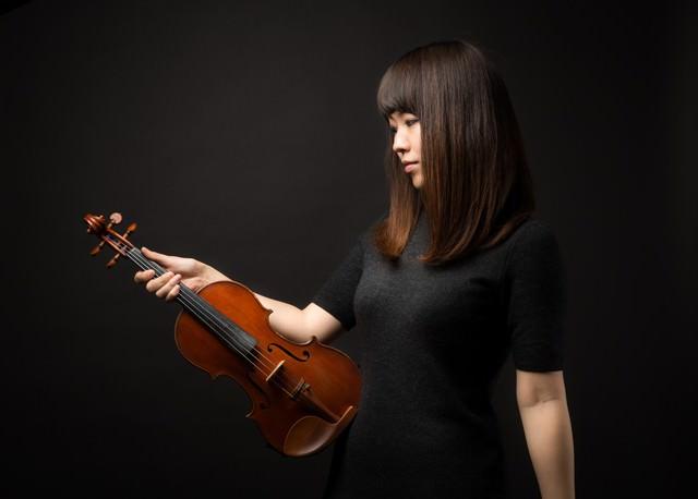 ヴァイオリンを見つめる女性の写真
