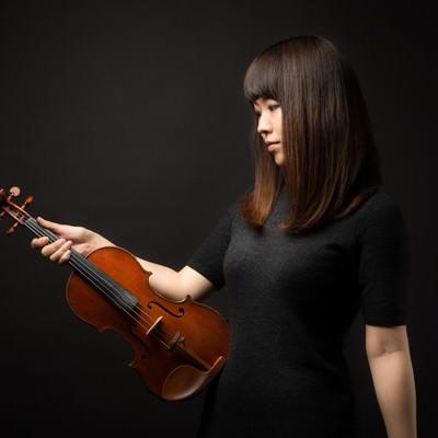 「ヴァイオリンを見つめる女性」の写真素材