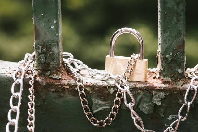 錆びた格子に繋がれた鎖と南京錠の写真