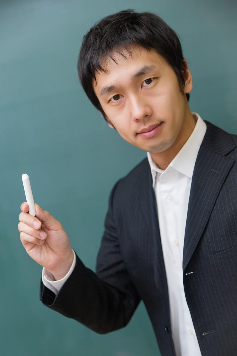 「チョークを持つスーツ姿の先生」の写真[モデル:大川竜弥]