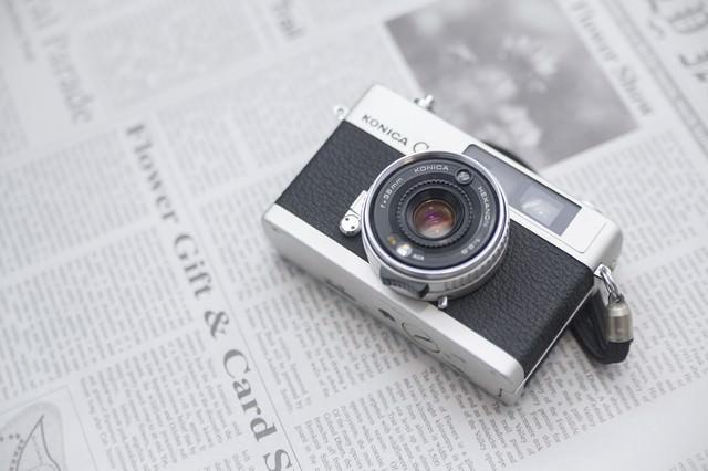 英文の新聞とレトロなカメラの写真