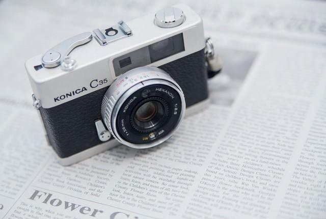 英文の新聞とカメラの写真