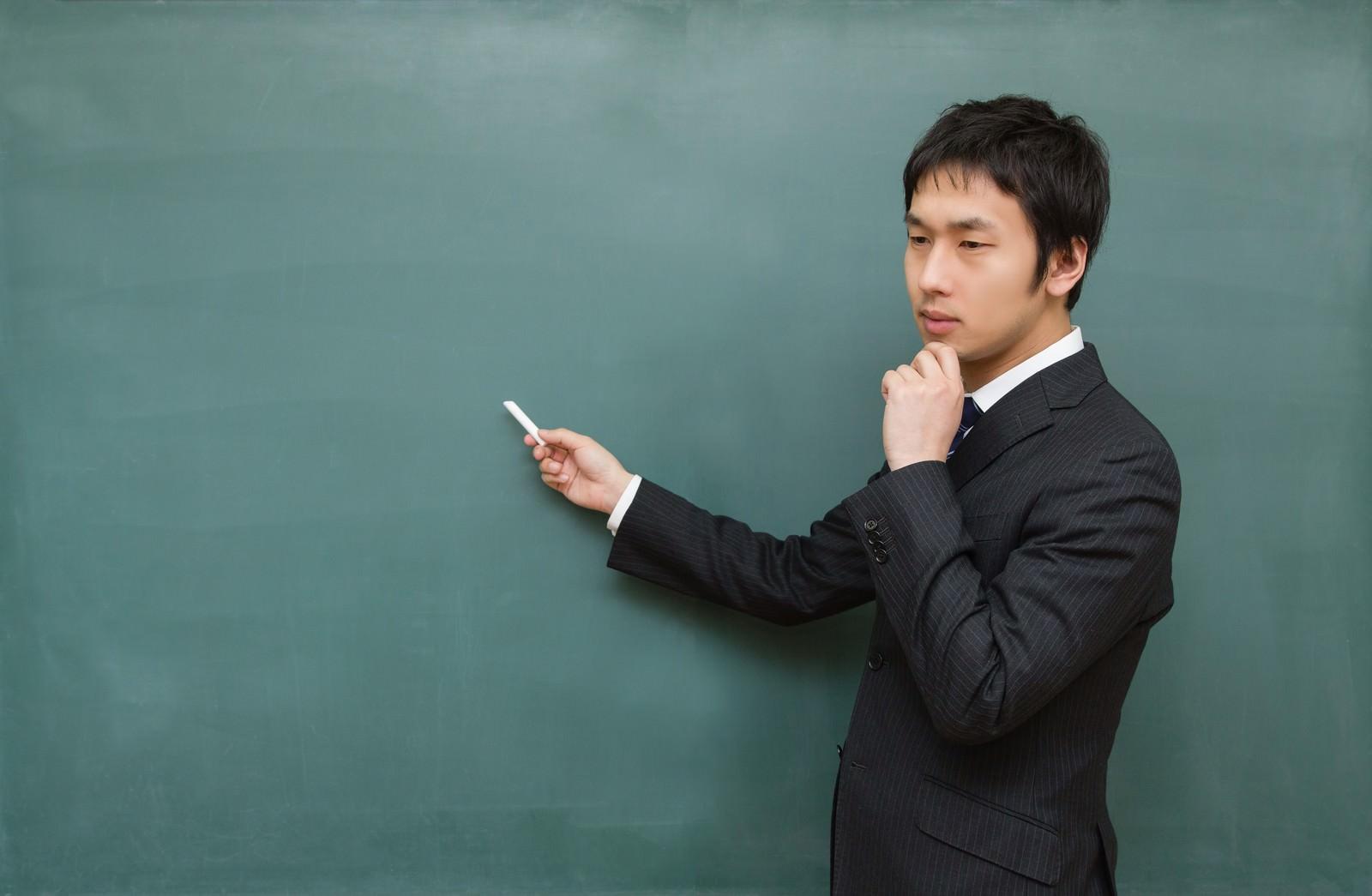 「黒板に向かって考えてしまう先生」の写真[モデル:大川竜弥]
