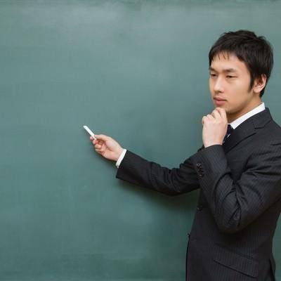 「黒板に向かって考えてしまう先生」の写真素材