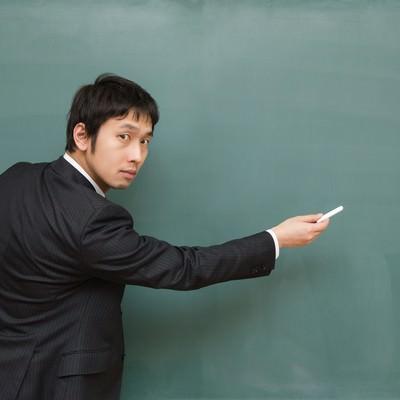 「ここ出ますよ!と黒板を指す先生」の写真素材