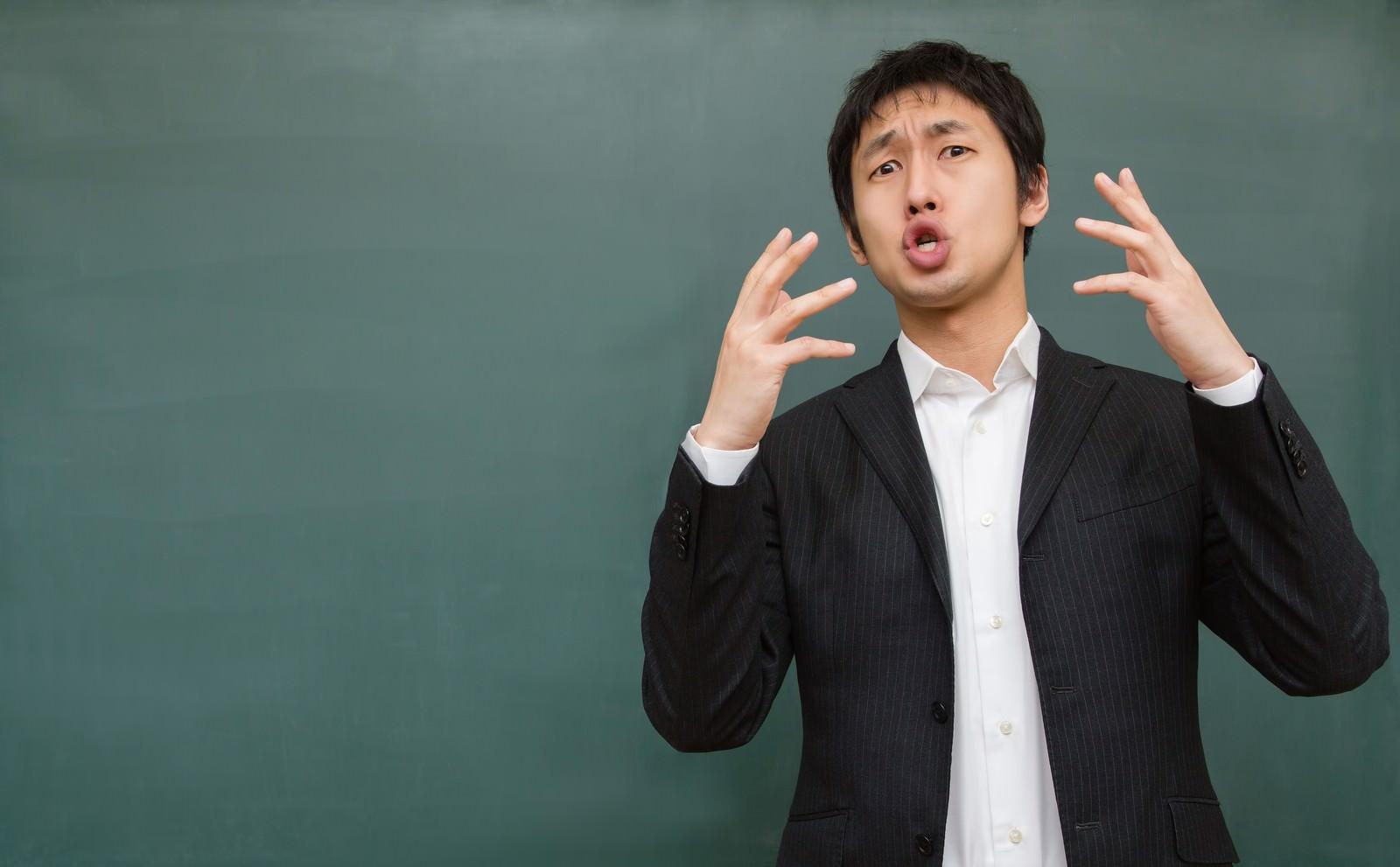 「両手を上げて訴えかける講師」の写真[モデル:大川竜弥]