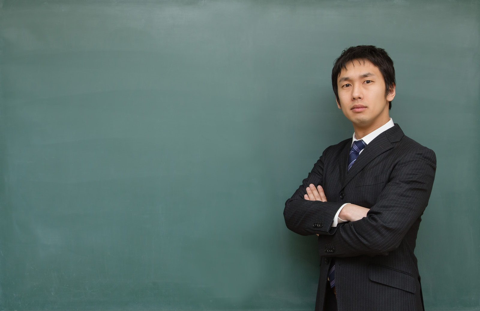 「腕を組み熱り立つ教師」の写真[モデル:大川竜弥]