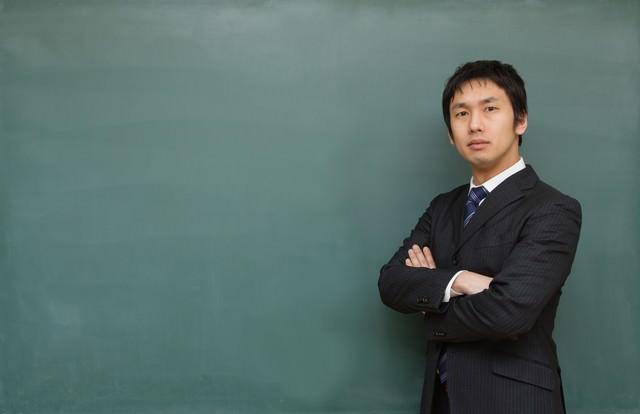 腕を組み熱り立つ教師の写真