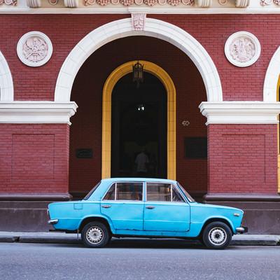 建物の前に駐車中の青い車(キューバ)の写真