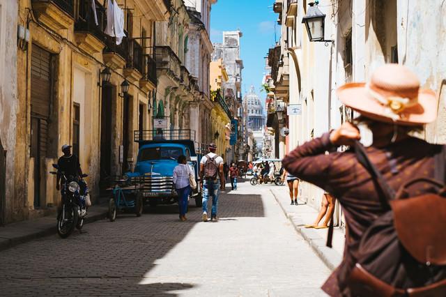 街を詮索する旅人とキューバの街並み