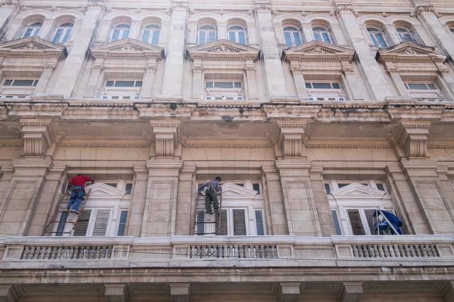 脚立で清掃中のホテルらしい建物(キューバ)の写真