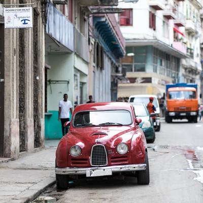 路肩に駐車している赤いSAABの写真
