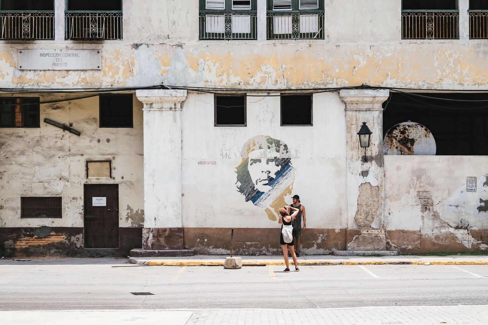 「チェ・ゲバラが描かれた壁画の前で写真を撮る観光客(ハバナ)」の写真