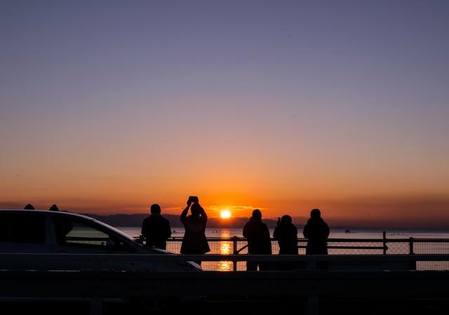 初日の出を撮影しようと集まる人々(シルエット)の写真