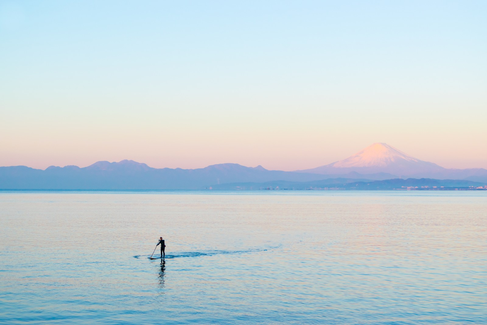 「富士山をバックにスタンドアップパドルボードを楽しむ男性」の写真