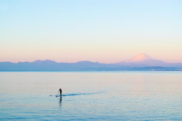 富士山をバックにスタンドアップパドルボードを楽しむ男性の写真