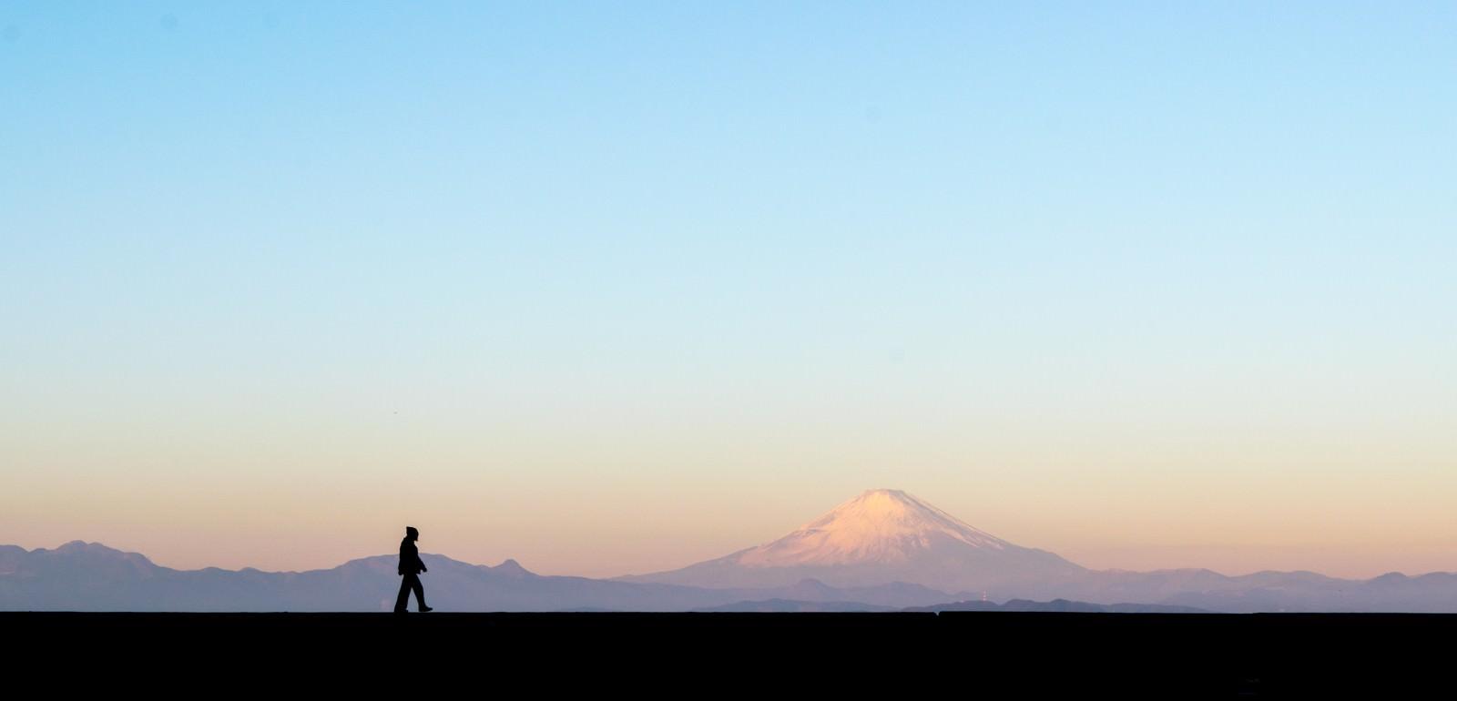 「富士山をバックに散歩する男性のシルエット」の写真