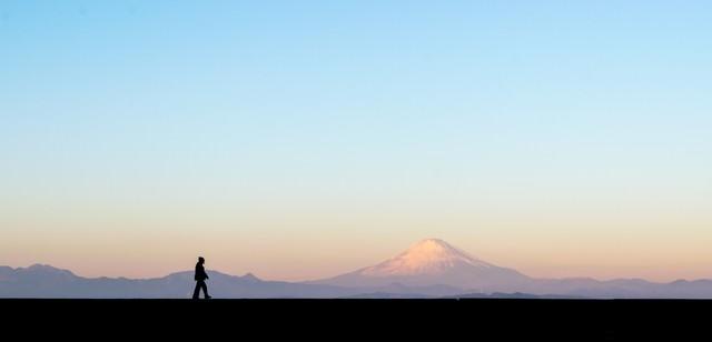 富士山をバックに散歩する男性のシルエットの写真